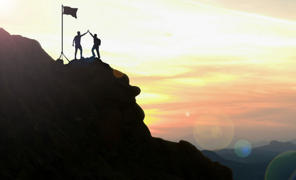 Photo of climbers celebrating on a mountaintop,